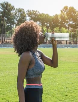 아프리카 머리 검은색 운동복과 회색 탑 서 있는 식수를 가진 젊은 흑인 운동선수 소녀는 자연 채광이 있는 배경에 잔디와 나무가 있는 빛에 반대합니다.