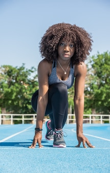 Young black athlete girl with afro hair crouching down ready to start a race wearing black sportswear and a gray top over blue running track and green trees and blue sky in the background