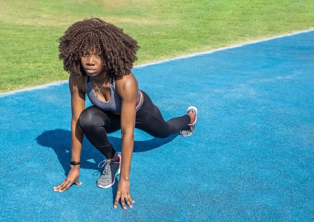 아프리카 머리를 웅크리고 검은색 운동복을 입고 회색 상의를 입고 파란색 달리기 트랙과 잔디 배경을 가진 젊은 흑인 운동선수