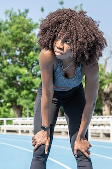 Young black athlete girl with afro hair standing with hands resting on her knees resting after a run looking to the side with blue running track and trees in the background