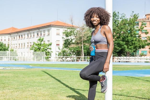 아프리카 머리를 가진 젊은 흑인 운동선수 여자가 등장성 음료와 함께 카메라를 보며 웃고 있다