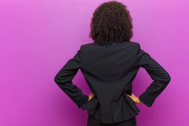 젊은 흑인 비즈니스 여자 느낌 혼란, 전체 또는 의심과 질문, 엉덩이에 손으로, 후면보기