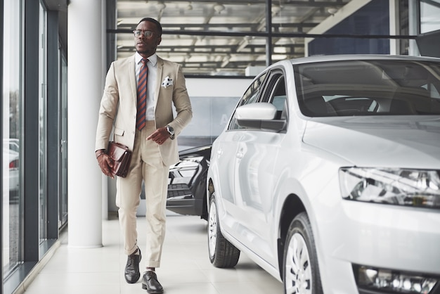 Young black businessman on auto salon. car sale and rent concept. rich african american man.