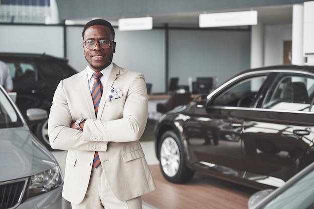 Young black businessman on auto salon. car sale and rent concept.