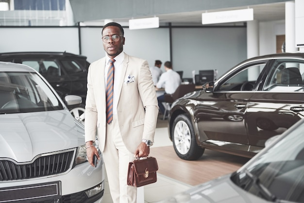 Young black businessman on auto salon. car sale and rent concept.