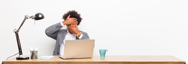 Young black businessman covering face with both hands