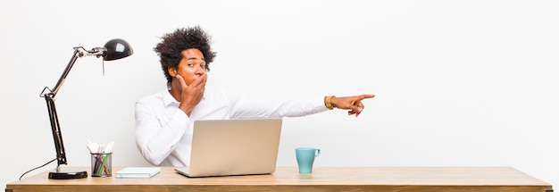 Young black businessman feeling happy, shocked and surprised, covering mouth with hand and pointing to lateral copyspace on a desk