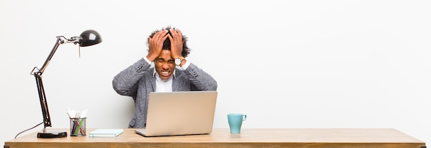 Young black businessman feeling stressed and anxious, depressed and frustrated with a headache, raising both hands to head on a desk