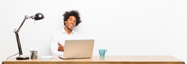 Young black businessman laughing happily with arms crossed, with a relaxed, positive and satisfied pose on a desk
