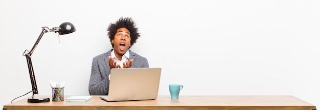 Young black businessman looking desperate and frustrated stressed unhappy and annoyed shouting and screaming