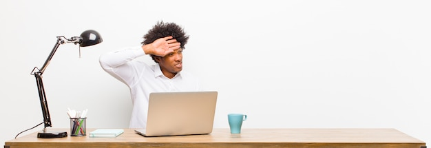 Young black businessman looking stressed, tired and frustrated, drying sweat off forehead, feeling hopeless and exhausted on a desk