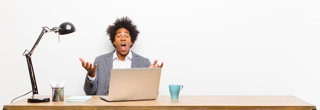 Young black businessman open-mouthed and amazed, shocked and astonished with an unbelievable surprise on a desk
