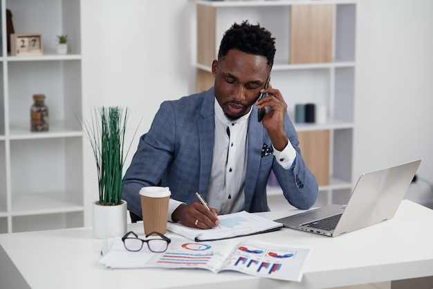 Young black businessman talking on mobile phone and working on laptop in modern white office, copy space