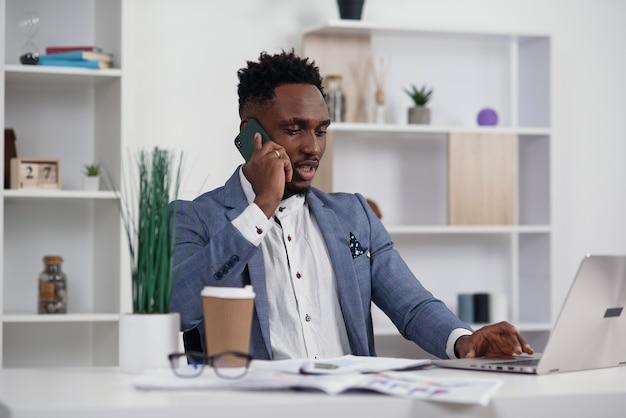 携帯電話で話していると現代の白いオフィスでラップトップに取り組んでいる黒人の若いビジネスマン、コピースペース