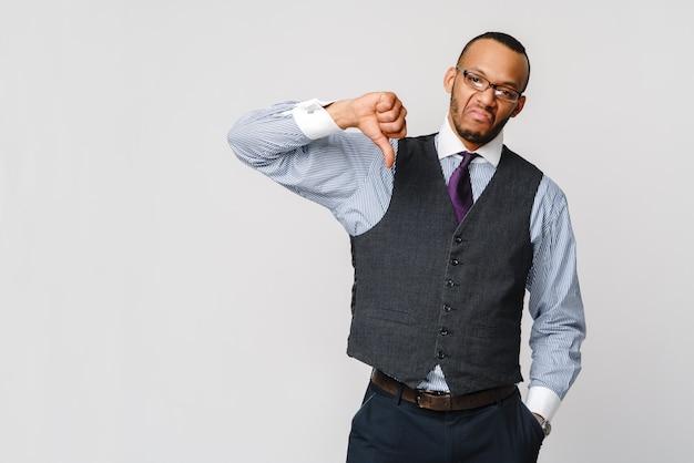 Молодой черный бизнесмен с выражением диссидентства серьезной неприязни с большими пальцами руки вниз в неодобрении.