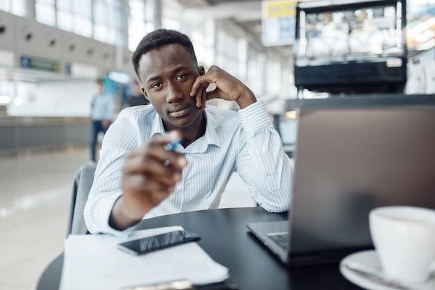 オフィスカフェでラップトップに取り組んでいる若い黒人実業家。成功したビジネスパーソンはフードコートでコーヒーを飲み、正装で黒人男性