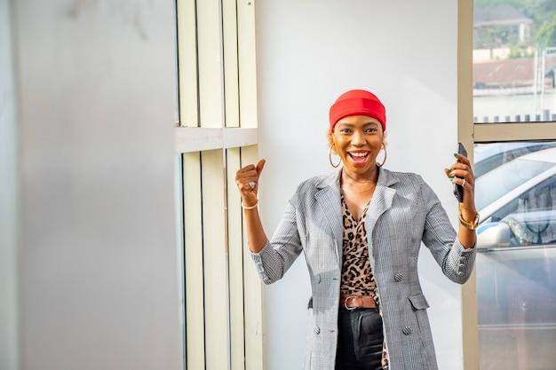 彼女の携帯電話を保持しながら祝う興奮と幸せを感じている若い黒人実業家