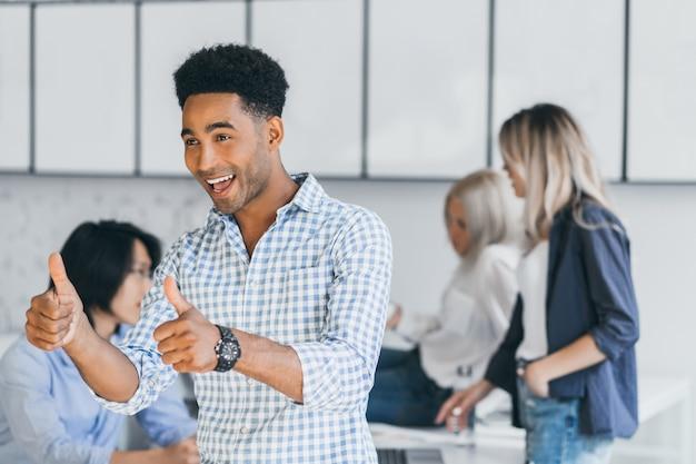 젊은 흑인 ceo는 외국 파트너와 성공적인 거래를하고 엄지 손가락을 보여주는 재미. 중국 동료와 함께 사무실에서 장난하는 행복 프리랜서 아프리카 전문가의 실내 초상화.