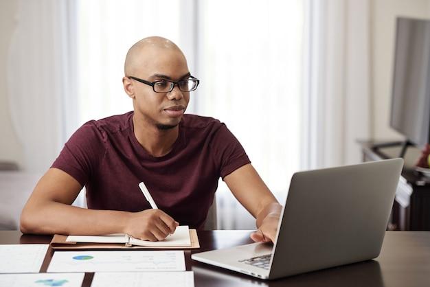 Молодой темнокожий предприниматель проверяет электронную почту и финансовые документы на ноутбуке и делает заметки в планировщике