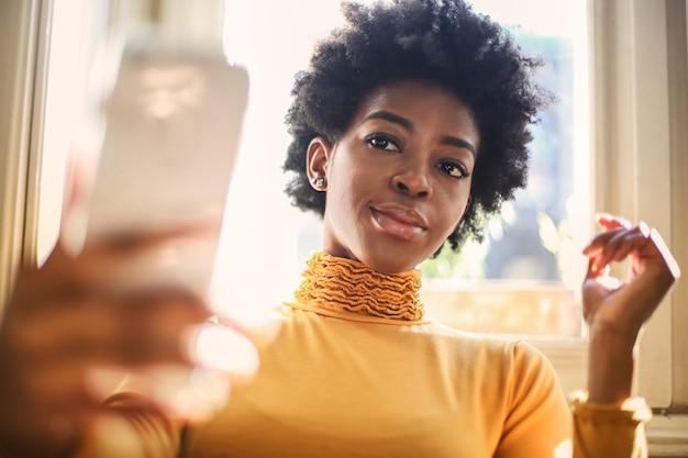 オレンジ色のセーターを着た若い黒人女性が窓の前の屋根で自分撮りをしている