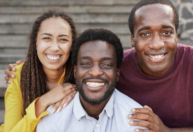 カメラで笑っている若い黒人の友人-スマートフォンで自分撮りをしているさまざまな肌の色のアフリカの人々