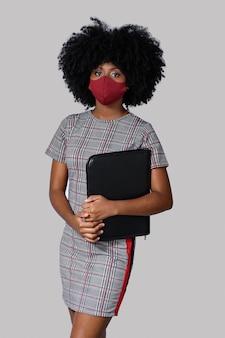 灰色の背景に分離されたフェイスマスクを身に着けている若い黒人少女