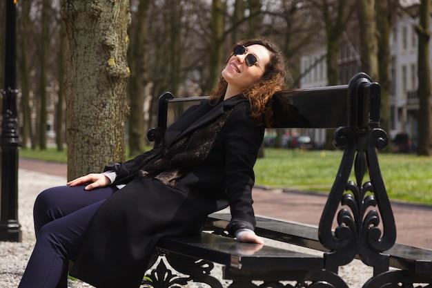 夏の公園のベンチに座っている若い黒眼鏡ベンチ少女の肖像画女性笑顔春コート長髪巻き毛ムード秋