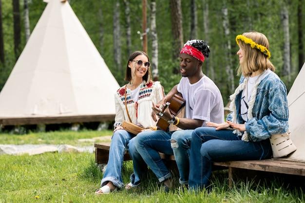 Молодой черный парень в бандане сидит с девушками в палатке и поет красивую песню в кемпинге
