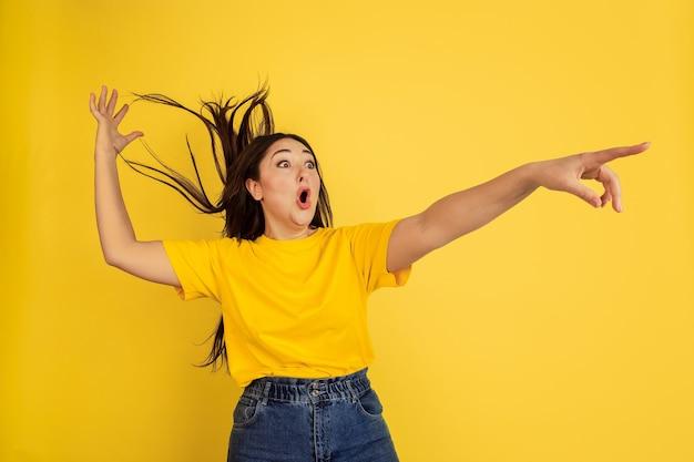 Молодая черноволосая женщина в желтой футболке у желтой стены
