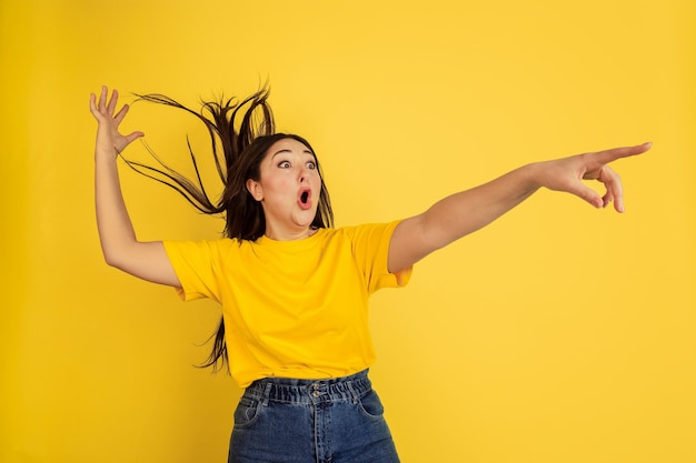 Young black-haired woman in yellow t-shirt against yellow wall