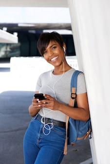 Young black lady standing outside and listening to music on smart phone