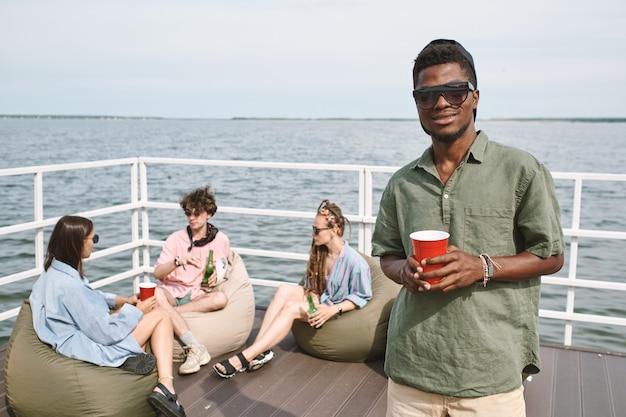 호수 옆 나무 부두에서 파티에 참석하는 젊은 흑인 남자는 술을 마시고 카메라를 보고 있다