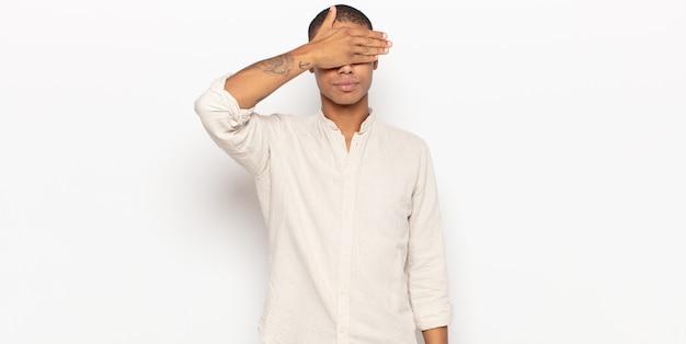 片手で目を覆っている若い黒人男性は、怖い、不安を感じ、不思議に思ったり、盲目的に驚きを待っている