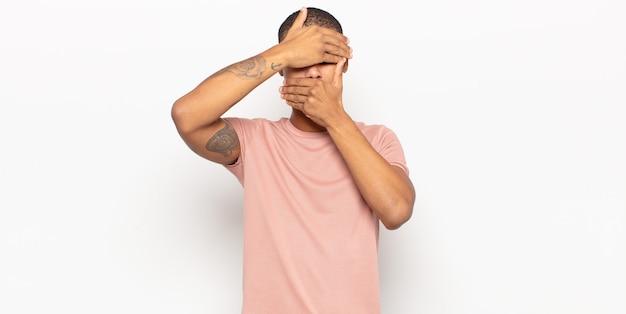 Молодой темнокожий мужчина закрывает лицо обеими руками, говоря