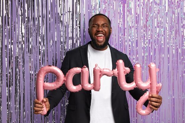 若い黒人男性はディスコで踊り、文字の形をした風船を持って、パーティーの壁に立ち、フォーマルなスーツを着て、屋内でポーズをとります。人と夜のエンターテイメントのコンセプト。結婚式前のスタッグパーティー
