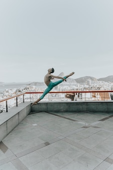 Young black man dancing on the rooftop of a building