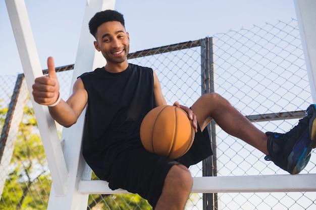 Молодой темнокожий мужчина занимается спортом, играет в баскетбол, активный образ жизни, летнее утро, улыбается, счастлив и веселится