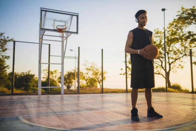 Молодой темнокожий мужчина занимается спортом, играет в баскетбол на рассвете, слушает музыку в наушниках, активный образ жизни, летнее утро