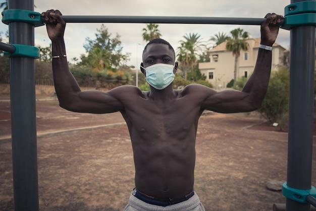 Молодой черный человек упражнения с маской для лица на открытом воздухе
