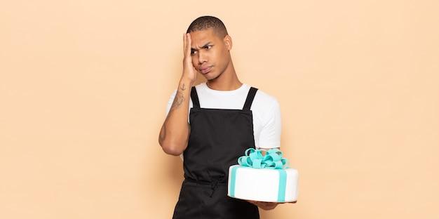 面倒で退屈で退屈な仕事をした後、退屈で欲求不満で眠そうな若い黒人男性が顔を手で持っている