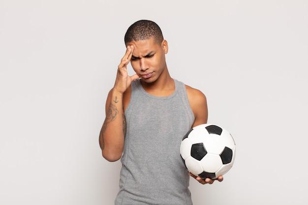 Молодой темнокожий мужчина скучает, расстраивается и хочет спать после утомительной, скучной и утомительной работы, держа лицо рукой