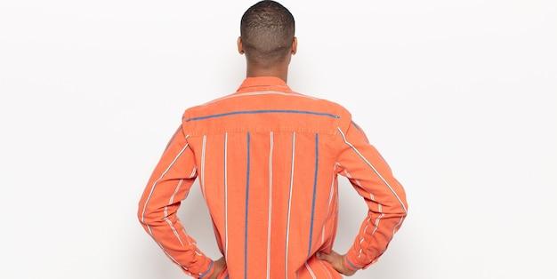 若い黒人男性は、混乱したり、満腹になったり、疑問や質問を感じたり、疑問に思ったり、腰に手を当てたり、背面図を表示したりします