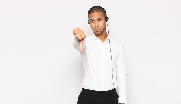Молодой темнокожий мужчина чувствует раздражение, злость, раздражение, разочарование или недовольство, показывая большой палец вниз серьезным взглядом
