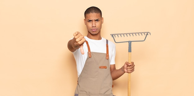젊은 흑인 남자가 십자가, 분노, 짜증, 실망 또는 불쾌감을 느끼고 심각한 표정으로 엄지 손가락을 보여줍니다.