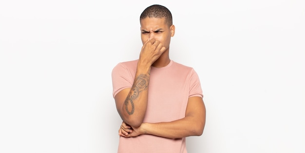 Young black man feeling disgusted, holding nose to avoid smelling a foul and unpleasant stench