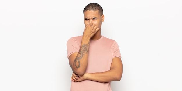 嫌悪感と不快な悪臭を嗅ぐのを避けるために鼻を保持している若い黒人男性