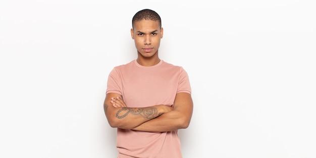Молодой темнокожий мужчина недоволен и разочарован, выглядит серьезным, раздраженным и злым со скрещенными руками