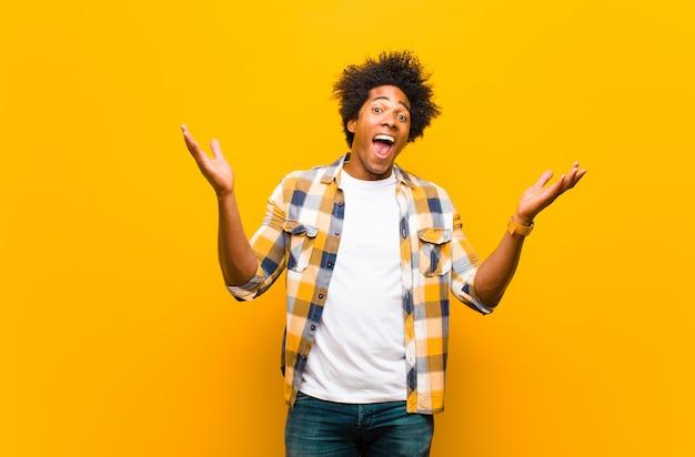 幸せ、興奮、驚き、またはショックを受けた笑顔、オレンジ色の壁に信じられないほどの何かに驚いた若い黒人男性