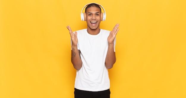 Молодой темнокожий мужчина чувствует себя счастливым, взволнованным, удивленным или шокированным, улыбается и удивляется чему-то невероятному