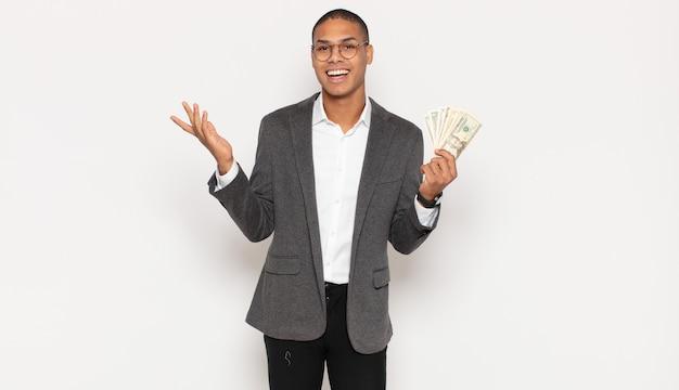 젊은 흑인 남자는 행복하고, 흥분하고, 놀라거나 충격을 받고, 웃고 있고 믿을 수 없는 일에 놀란다